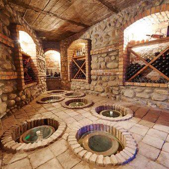 Zorenje vina v velikih glinastih vrčih v gruzijski vinski kleti